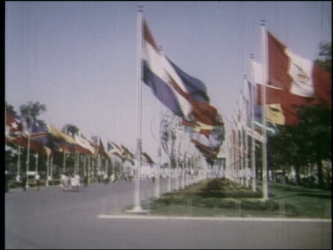 1964 side point of view promenade lined by flags with unisphere in background at ny world's fair - weltausstellung in new york stock-videos und b-roll-filmmaterial