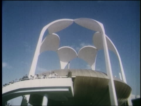 1964 side point of view tilt down past exterior of suspended round movie theater with crowd in front / ny world's fair - 1964年点の映像素材/bロール