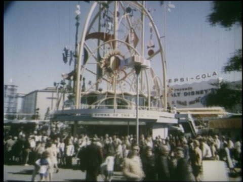 1964 side point of view tilt up of sculpture on top of building surrounded by crowd at ny world's fair - 1964年点の映像素材/bロール