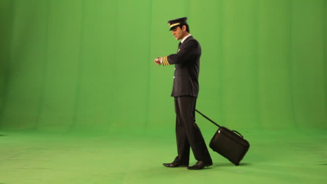 vidéos et rushes de side profile of a pilot pulling a luggage and watching his wristwatch - fond vert