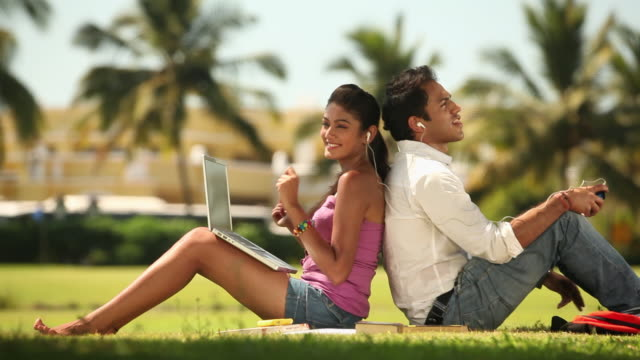 side profile of a young couple sitting back to back and listening music - dancing back to back stock videos & royalty-free footage