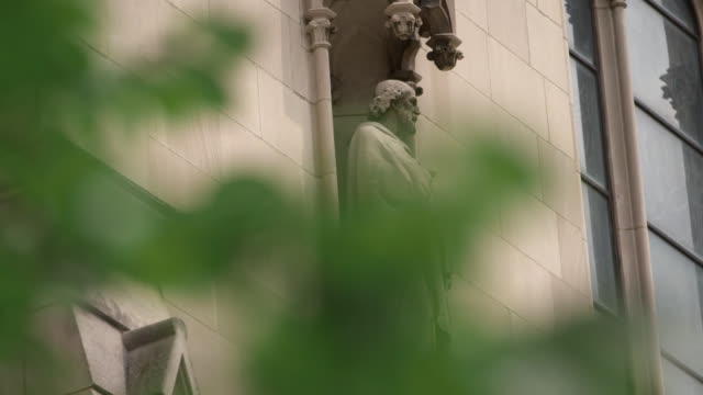 side profile shot through the trees of a statue on the outside of saint paul cathedral in pittsburgh pennsylvania on august 15 2018 - religion or spirituality bildbanksvideor och videomaterial från bakom kulisserna
