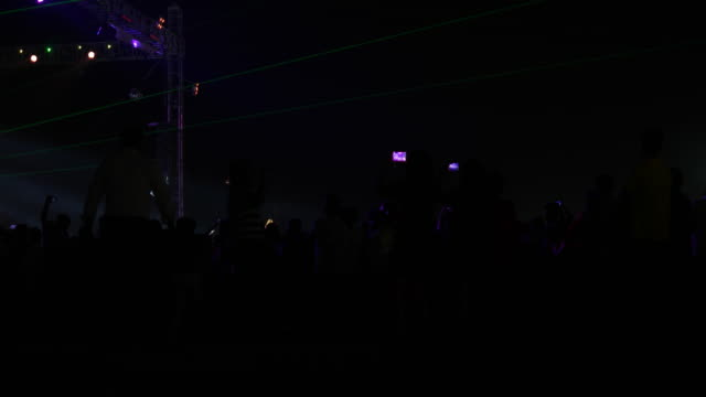 Side profile view of a crowded concert and stage venue at an outdoor performance area of a music festival during night with flashing stage lights and laser display