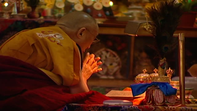 side rearpov of hh the dalai lama meditating with clasped hands in the tsuglagkhang temple hh the 14th dalai lama tenzin gyatso lives in exile in... - meditating stock videos & royalty-free footage