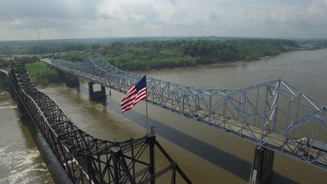 side reveal orbit of american flag reveal down bridge - drone aerial 4k mississippi river bridge and barge 1of14, everglades, gulf delta, new orleans, st louis, with cruise boats sailing and wildlife.mov	4k transportation - louisiana stock videos & royalty-free footage