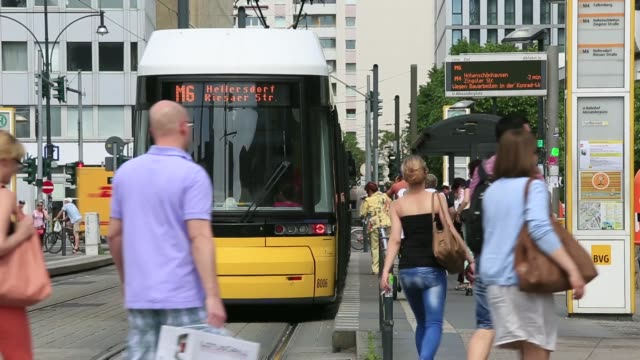 Side shot a tram arrives into a station platform in Berlin Germany on Wednesday May 21 Side view passengers board tram from platform Commuters run to...