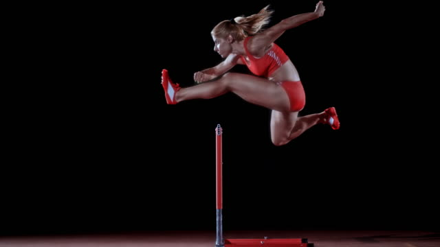 stockvideo's en b-roll-footage met slo mo ld side shot of a caucasian female hurdler jumping over a hurdle on black background - atlete