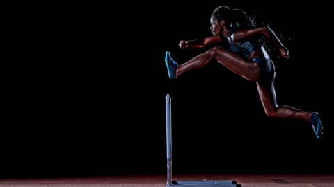 slo mo ld side shot of a female african-american hurdler jumping over a hurdle on black background - track and field stock videos & royalty-free footage