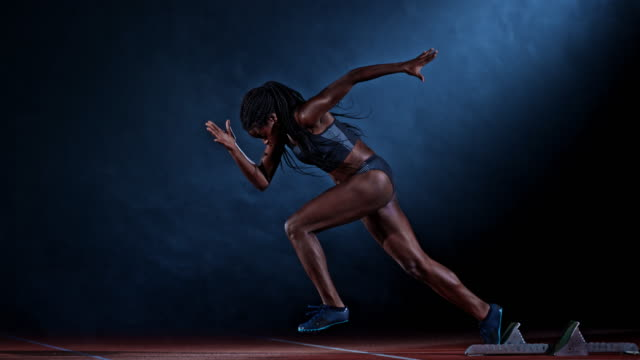 slo mo ts side shot of a female african-american sprinter starting - pista di atletica leggera video stock e b–roll