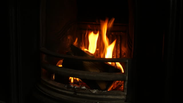 side shot of a log being placed onto a burning fireplace - coal stock videos & royalty-free footage