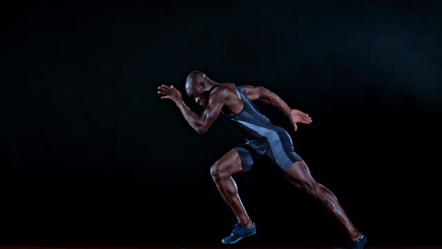 SLO MO TS Side shot of a male African-American sprinter starting from the starting block