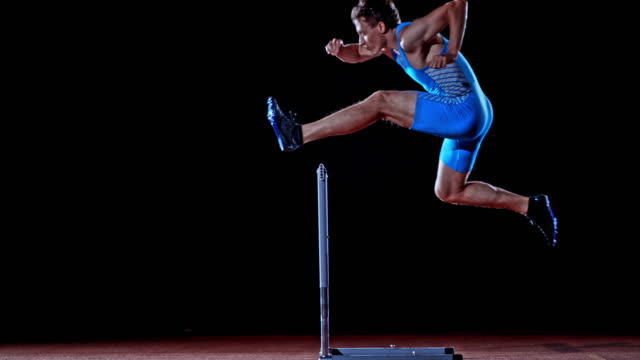 slo mo ld side shot of a male caucasian hurdler jumping over a hurdle on black background - track and field event stock videos & royalty-free footage
