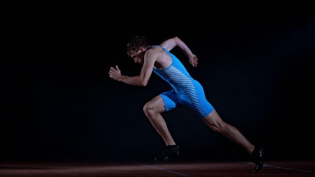 slo mo ts side shot of a male caucasian sprinter starting from the starting block - トラック競技点の映像素材/bロール