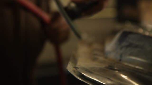 Side shot of a mechanic filing an auto part