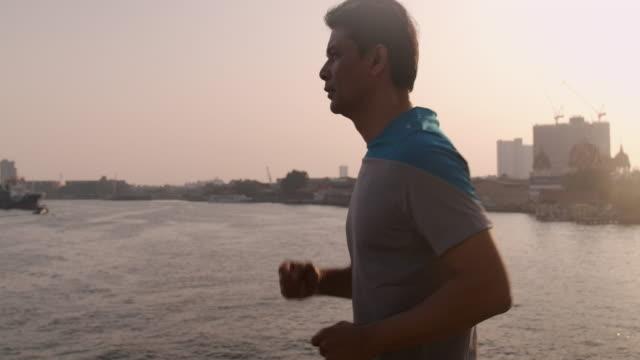 seitenaufnahme des asiatischen seniors geschwindigkeit zu fuß über die brücke über sonnenuntergang. - non urban scene stock-videos und b-roll-filmmaterial