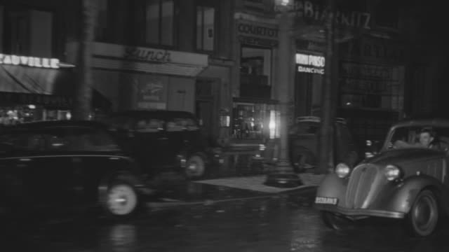 ms side pov shot of auto driving in rain through residential and commercial area back right passing  people, shops and other period cars - ladenschild stock-videos und b-roll-filmmaterial
