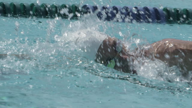 CU Side POV SLO MO Shot of Female swimmer in lane, swimming freestyle, breathing deeply / Davis, California, United States