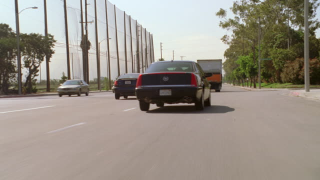 MS TS Side POV Shot of four door Cadillac driving erratic and weaving through traffic
