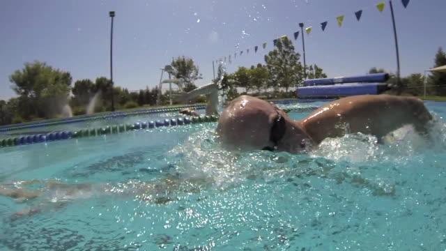CU Side POV SLO MO Shot of male, baby boomer, swimming freestyle / Davis, California, United States