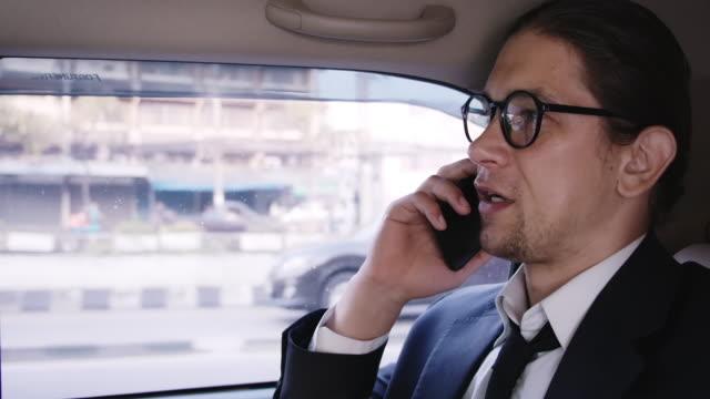 vídeos de stock, filmes e b-roll de tiro lateral de homem em terno de negócios usando telefone no banco de trás de um carro. - passenger