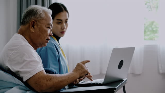 side shot of nurse helping senior man with laptop. - 70 79 years stock videos & royalty-free footage