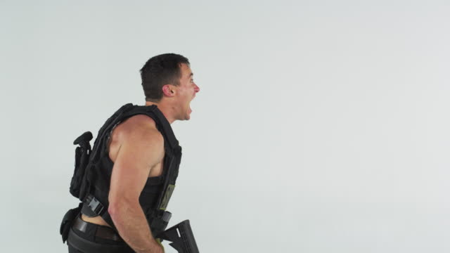 Side shot of soldier screaming, then shooting gun. Shot in slow motion against a grey screen.