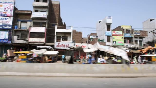 ms side pov shot of streets of old lahore from car / old city of lahore punjab pakistan - punjab pakistan bildbanksvideor och videomaterial från bakom kulisserna