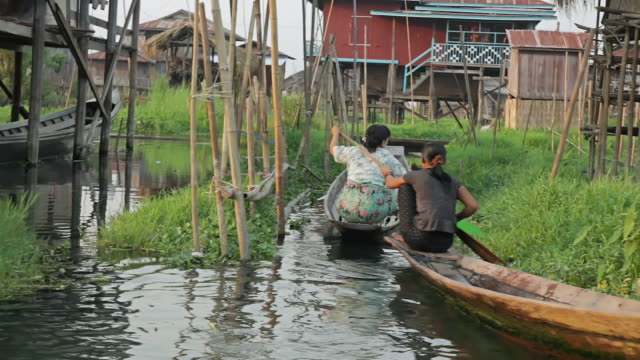 ms side pov shot of two women on boats paddling through neighborhood with houses constructed on inle lake (daytime) / inle lake, shan state, myanmar  - shan state stock videos & royalty-free footage