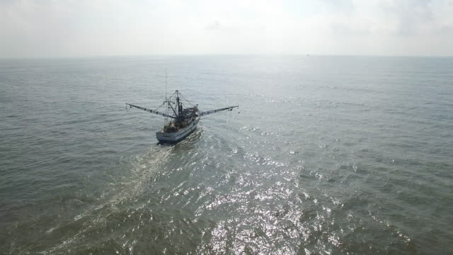 side to behind pull away shrimp fishing boat - drone aerial view 4k prawn fishing, shrimp boat, trawler, trawling for ocean fish in the open sea, heavy waves and nets in the water on louisiana, mississippi coast, gulf coast 4k transportation - trawler stock videos & royalty-free footage