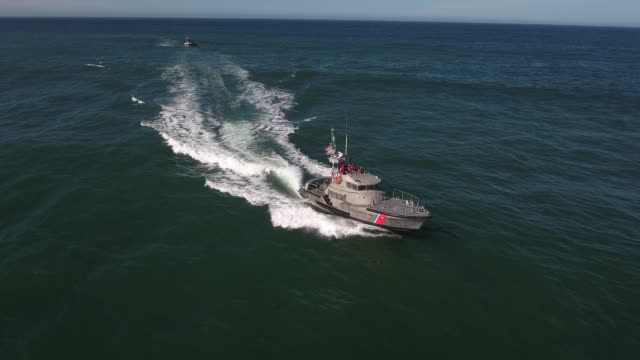 side tracking coast guard boat, rough seas, rouge wave crashing over boat water, Drone aerial video, 4k, rescue, marine, pacific, tide, surge, danger, dangerous waves raw.mov