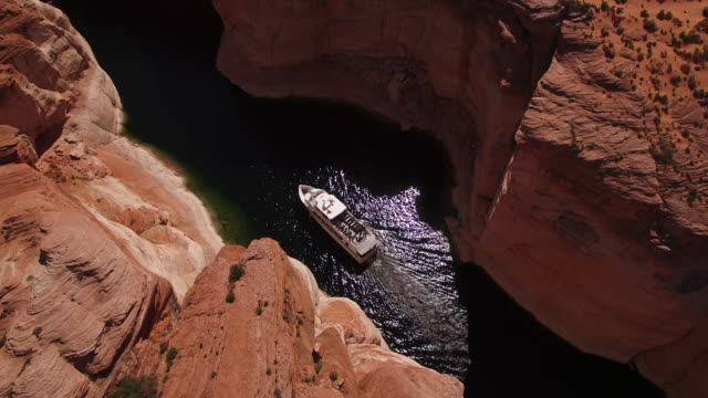 side tracking of boats on lake powell narrow water away 4k, drone aerial view of kayak and boat on lake powell reservoir and colorado river, with beautiful sand stone grand canyon and water reflection located in glen canyon, arizona - lake powell stock videos & royalty-free footage