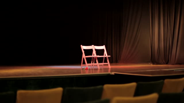 side tracking shot across two chairs on a stage in a theatre. - stage performance space stock videos & royalty-free footage