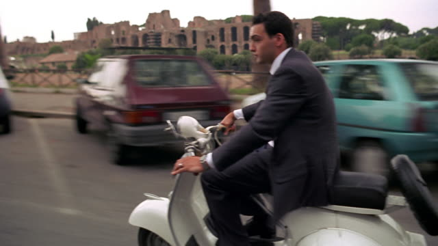 Side tracking shot businessman riding scooter past parked cars / Palatine Hill + Circus Maximus ruins background / Rome