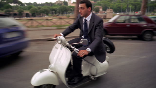Side tracking shot businessman riding scooter past parked cars / ruins of Palatine Hill in background / Rome, Italy