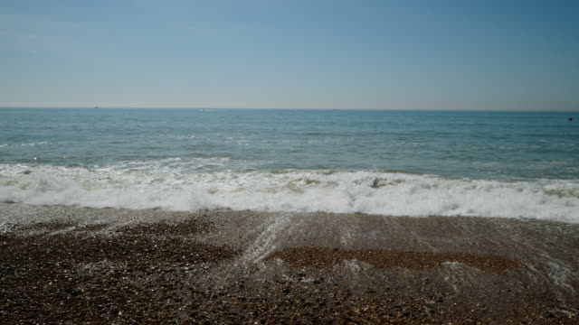 side tracking shot of waves rolling onto brighton beach. - riva dell'acqua video stock e b–roll