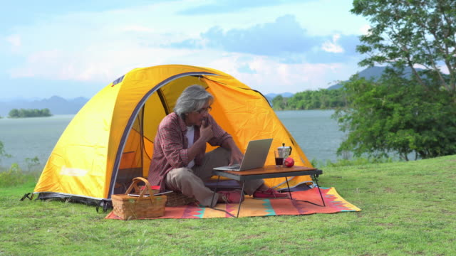 side view: alone senior man spending weekend time relaxing by camping and working on a laptop along lake - leisure activity stock videos & royalty-free footage