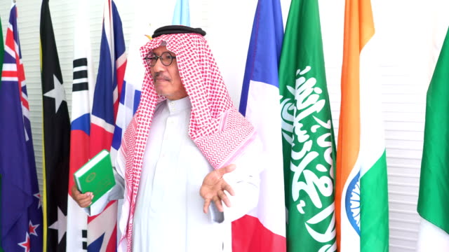 side view: arab dignified and old businessman interview to press on national flag - middle east stock videos & royalty-free footage