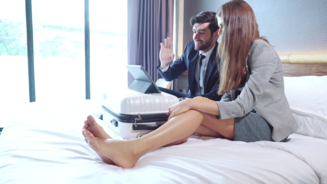 side view: asian businessman and russian beautiful businesswoman wearing formal clothes sitting on white bed having business meeting, discussing on digital tablet laying on  wheeled luggage with positive emotion of smiling in the luxury hotel resort room. - 25 29 years stock videos & royalty-free footage