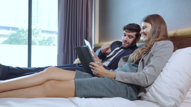side view: asian businessman and russian beautiful businesswoman wearing formal clothes sitting on a white bed and discussing business on a digital tablet with relaxation and positive emotion of smiling in the luxury hotel resort room. - 25 29 years stock videos & royalty-free footage
