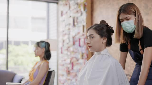 vidéos et rushes de vue de côté: cheveux teins asiatiques jeune femme barber en tant que coiffeur service un cheveux de coupe, couleur cheveux teins de belle femme caucasienne cheveux bruns dans la boutique de salon, concept de la vie d'un travailleur essentiel, petite en - brown hair
