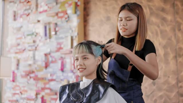 seitenansicht: asiatische junge frau friseur als friseur vorbereiten haare, indem sie sie an den service färbte haare von asiatischer schöner frauenfarbe färbten haaren im salonladen, lebenskonzept eines essentiellen arbeiters, kleines unternehmen. - 20 29 years stock-videos und b-roll-filmmaterial