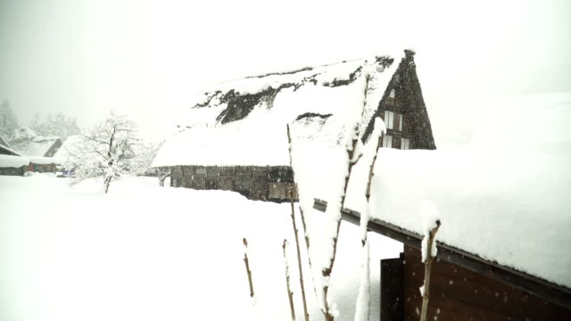 side view: big japanese snow-covered house in  shirakawago village - shack stock videos and b-roll footage