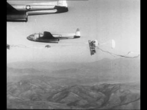 side view c119 flying boxcars cargo planes drop supplies via parachute over korea jeep drops and falls to earth attached to parachute / deployed... - korean war stock videos & royalty-free footage