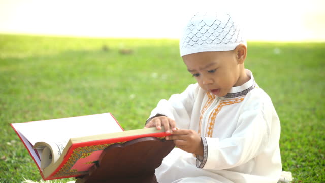 side view: cheerful young boy in traditional garments try to read  quran in public park by himself - koran stock videos & royalty-free footage
