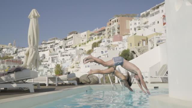 side view couple jumping in swimming pool slow motion - サーフパンツ点の映像素材/bロール