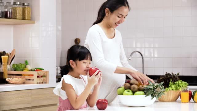 vídeos de stock, filmes e b-roll de vista lateral: ajuda filha mãe grávida na cozinha moderna - família monoparental
