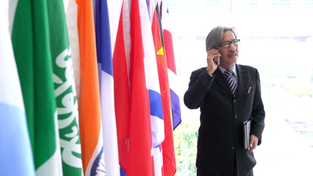 side view: dignified and old businessman communicate with colleague on smartphone on national flag - uruguaian flag stock videos & royalty-free footage