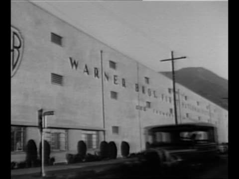 side view ext paramount pictures entrance / ext building with logo similar to that of rko pictures / ws ext universal pictures studio in background... - 1930 stock-videos und b-roll-filmmaterial