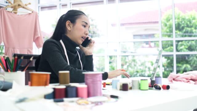 seitenansicht: weibliche mode-designer diskutieren ihre arbeit an ihrem telefon im büro zu hause - 20 29 years stock-videos und b-roll-filmmaterial