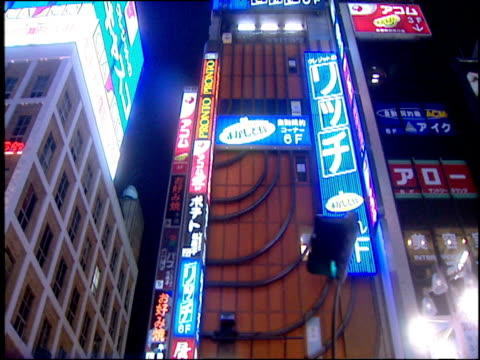 Side view from car of neon signs on Tokyo buildings at night